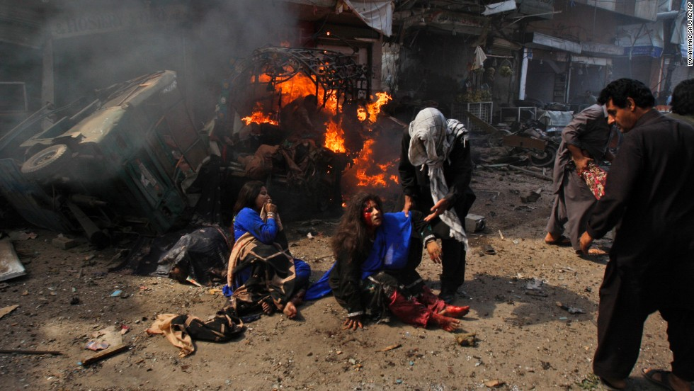 People help injured women at the site of the explosion in Peshawar on September 29.