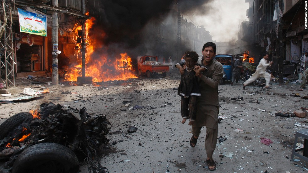 A man rushes a child away from the site of the blast on September 29.