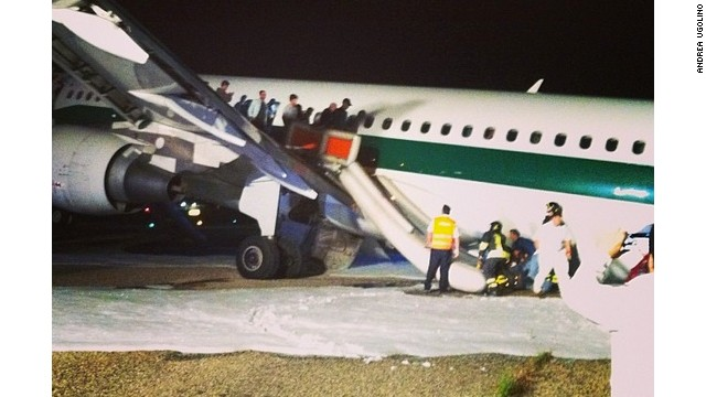 Passengers evacuate an Alitalia flight that was forced to make an emergency landing at Rome's Fiuminco airport on Sunday