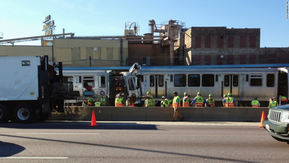 Emergency personnel investigate the scene on September 30 after a Chicago Transit Authority train ran head-on into another train that was stopped at a Blue Line station in Forest Park, Illinois.