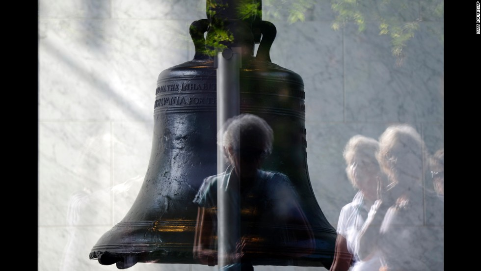 Visitors to Independence National Historical Park are reflected in the window of the closed building housing the Liberty Bell, on October 1 in Philadelphia.