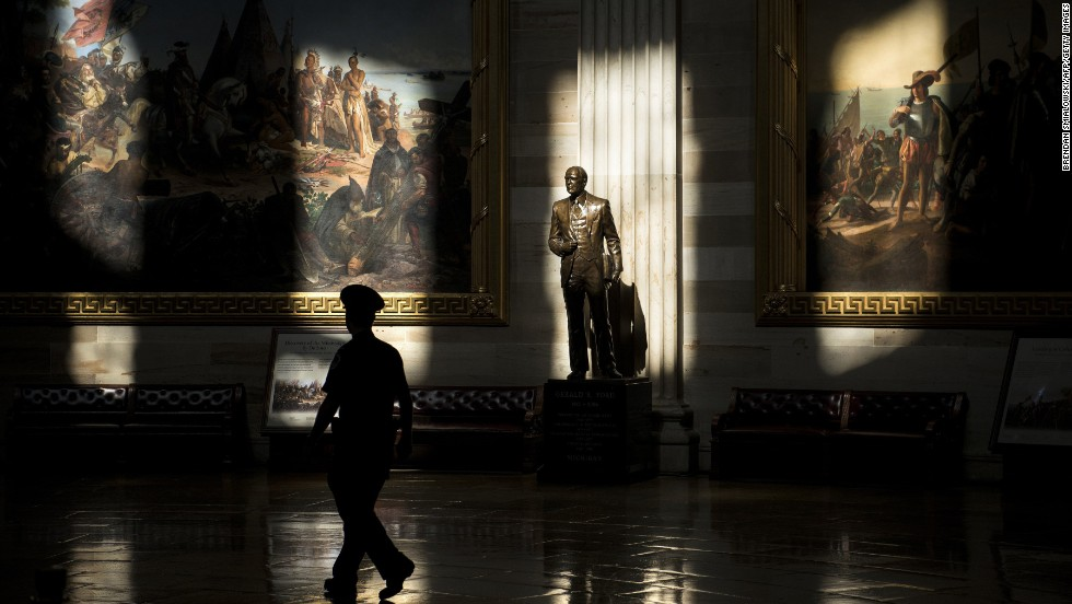 A U.S. Capitol police officer walks past a statue of Gerald Ford in the rotunda on Tuesday, October 1. The Capitol is closed to tours because of the government shutdown.
