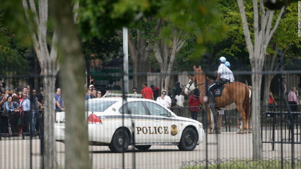 A Secret Service vehicle joins law enforcement officers riding on horseback.