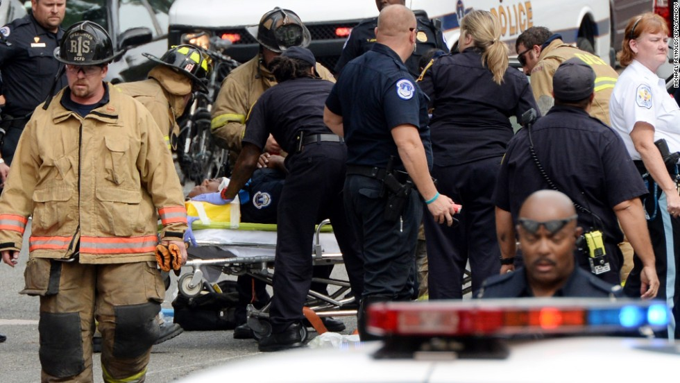 Emergency personnel put an unidentified police officer on a stretcher.