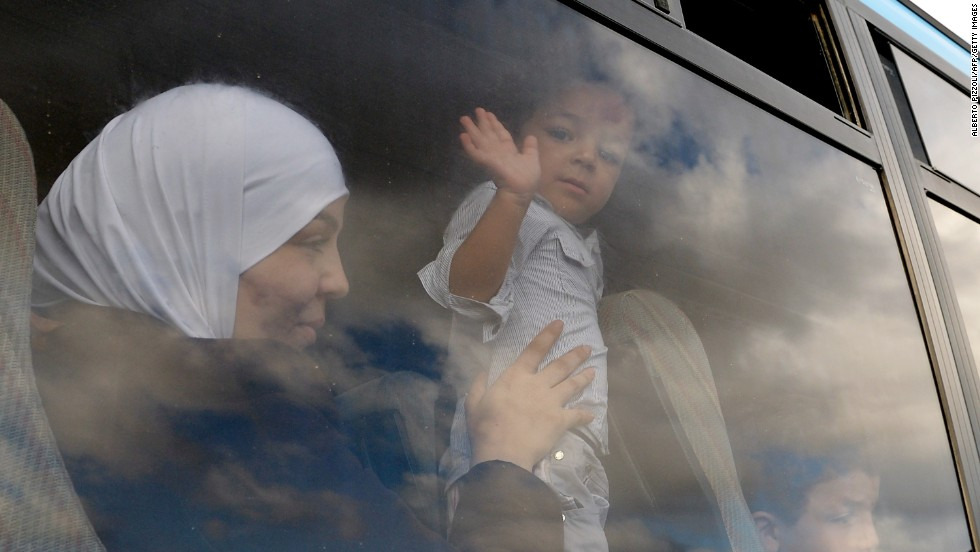 "OCTOBER 4 - LAMPEDUSA, ITALY: A child migrant waves from the window of a bus taking him to Sicily. As the closest Italian island to Africa, <a href=""http://www.cnn.com/video/?/video/world/2013/10/03/lampedusa-paths-of-immigrants-lkl-dos-santos.cnn"">Lampedusa is a destination for tens of thousands of refugees</a> every year. Many die during perilous attempts to cross the Mediterranean. 300 asylum seekers are <a href=""http://www.cnn.com/2013/10/04/world/europe/italy-migrant-boat-sinks/index.html?hpt=hp_t1"">feared dead after a boat capsized</a> just half a mile off the coast on Thursday."