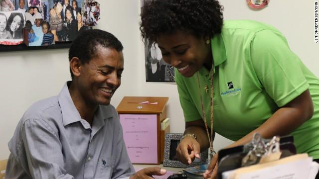 Jekisha Elliott looks at Geremen Teklehaimanot's phone, which was stuck on a health insurance exchange website.