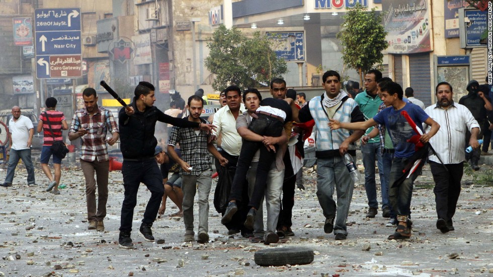 People carry a man near Ramses Square in Cairo.