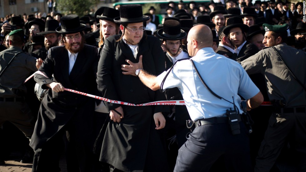 Police try to hold back Orthodox men and children from reaching the vehicle carrying the rabbi's body.
