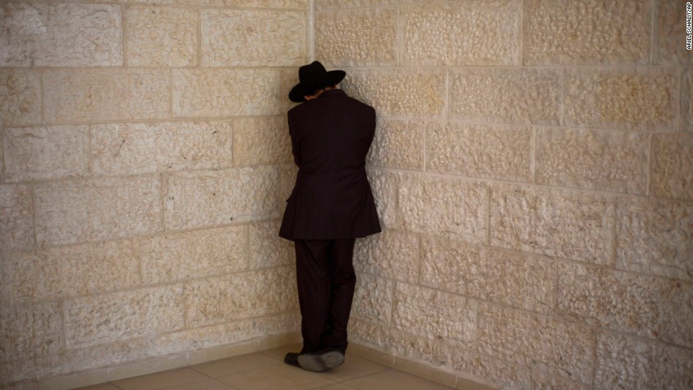 A man weeps outside Yosef's home in Jerusalem after hearing about the rabbi's death.