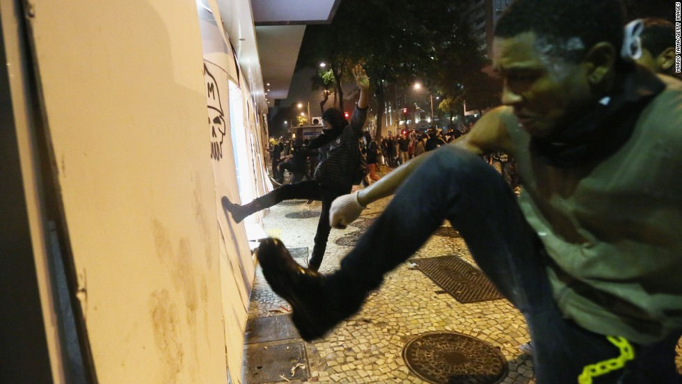 Protesters kick in wood panels blocking a bank location on October 7 after tear gas was fired by the police to disperse protesters.