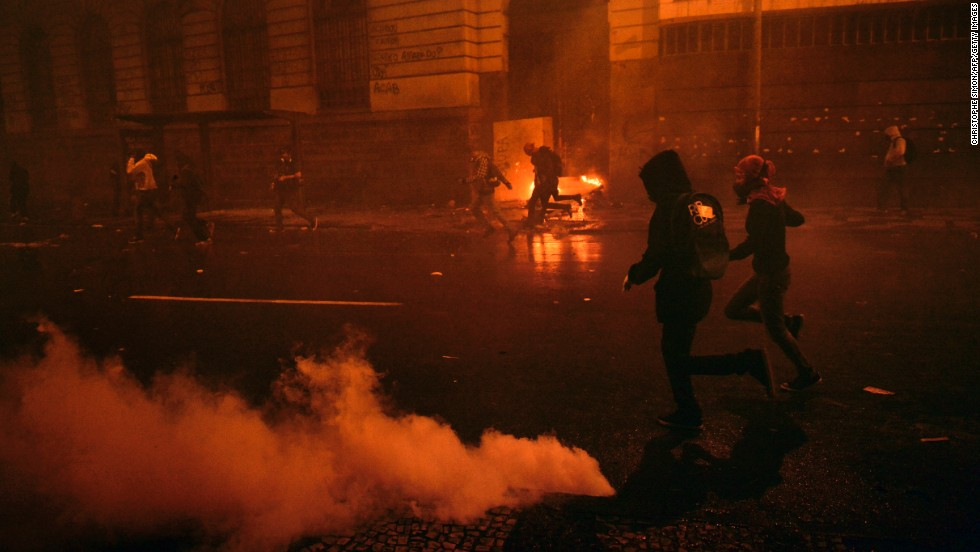 Demonstrators run after riot police used tear gas to disperse the crowds during the October 7 Rio protests.