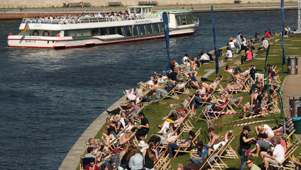 People enjoy an outdoor bar along the banks of the River Spree in Berlin.  Areas on both sides of the river have been transformed into bars and community gardens, artists' studios and underground nightclubs where residents and tourists  can gather.
