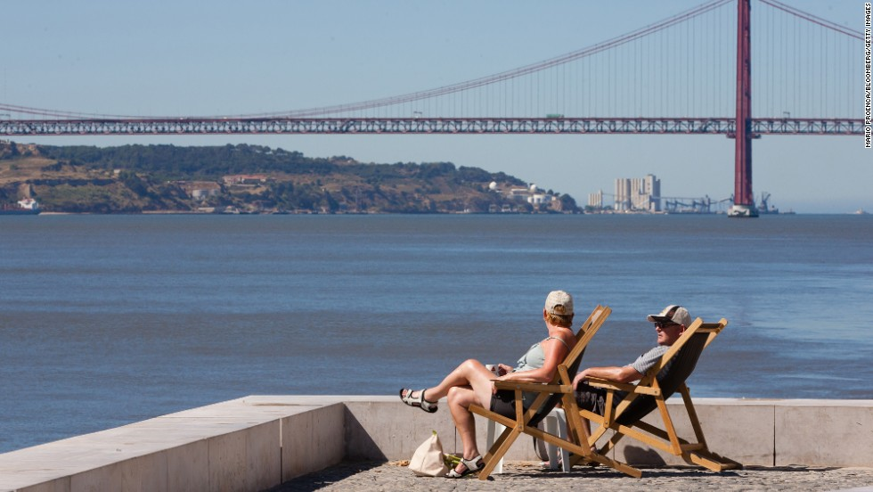 "Tourists sit in the sun at Cais do Sodre overlooking the River Tagus and the ""25th of April Bridge"" bridge in Lisbon, Portugal. Once known for its seedy bars and brothels, today it boasts hot clubs and great restaurants."