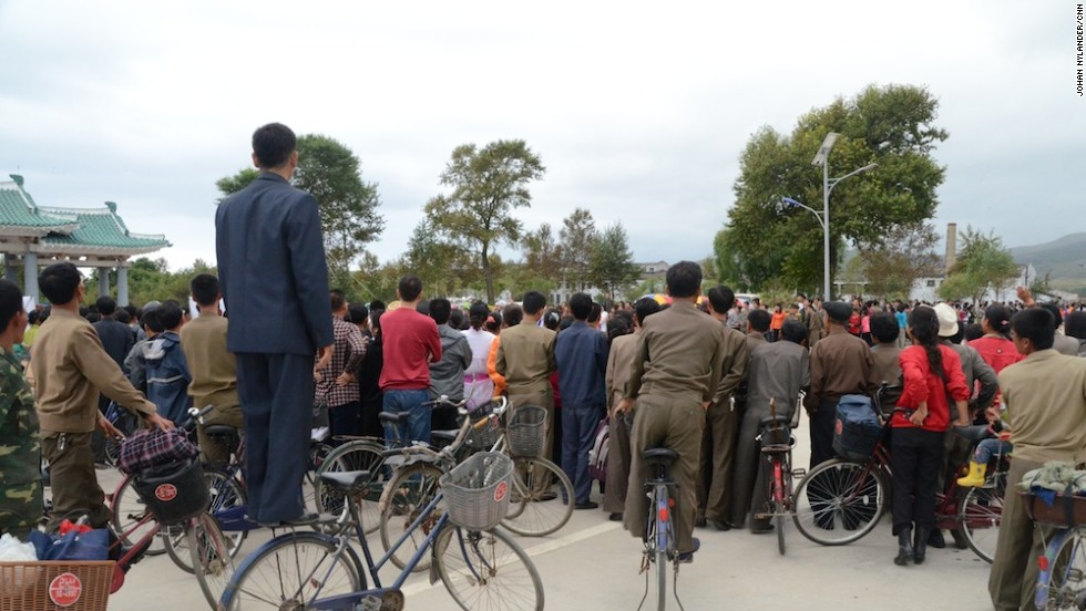 Huge crowds -- some of whom standing on their own bikes -- as they await cyclists by the race finish line in Rason.