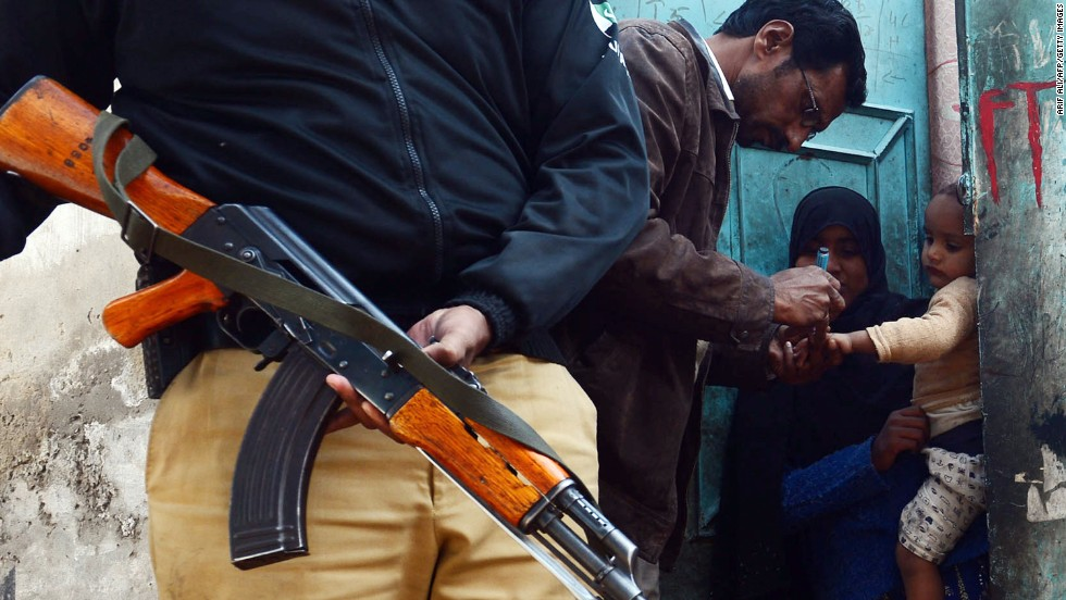 Efforts to stamp out the crippling disease have been hampered by resistance from the Taliban, who have banned vaccination teams from some areas. A Pakistani policeman stands guard as a polio vaccination worker marks a child after immunization with anti-polio drops an infant in Lahore on December 21, 2012.