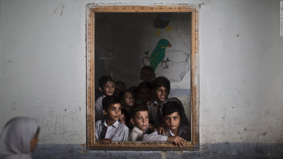 "OCTOBER 9 - RAWALPINDI, PAKISTAN: Boys look out of the window of their classroom at their schoolmates chanting prayers to commemorate the anniversary of Malala's <a href=""http://www.cnn.com/2013/10/07/world/asia/taliban-malala/index.html?hpt=hp_c3"">shooting by Taliban</a>. One year after a bullet tried to silence <a href=""http://www.cnn.com/2013/10/09/world/asia/malala-shooting-anniversary/index.html?hpt=hp_c3"">Malala Yousufzai's demand for education</a>, she has published a book and is a contender for the Nobel Peace Prize."