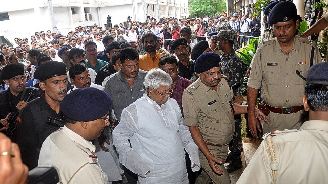 Lalu Prasad Yadav (C), a former Indian federal minister, whose Rashtriya Janata Dal party supports the ruling coalition, walks into court before a hearing in Ranchi, Jharkhand on September 30, 2013. An Indian court convicted, Yadav, a regional government ally, of corruption making him one of the first politicians set to be disqualified from parliament under new rules barring criminal MPs. AFP PHOTO/ STRSTRDEL/AFP/Getty Images