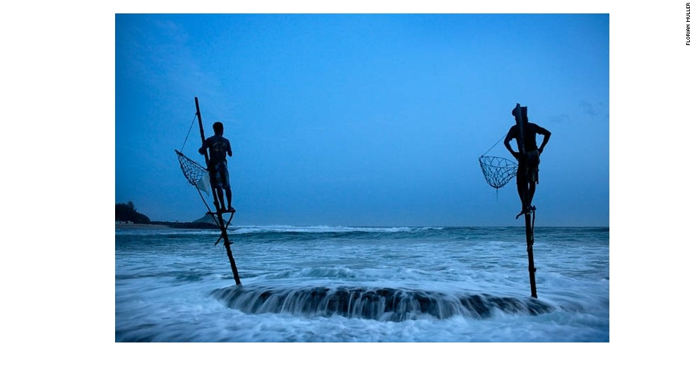 At dawn, fishermen Sunil Nishanti (left) and Anil Madushanka sit on wooden stilts they both inherited from their fathers. Sunil and his family lost almost everything when the tsunami of 2004 flooded the bay where they lived on the coast of Ahangama, Sri Lanka. For now, he still earns his living from fishing but his catch is barely enough to feed his own family.
