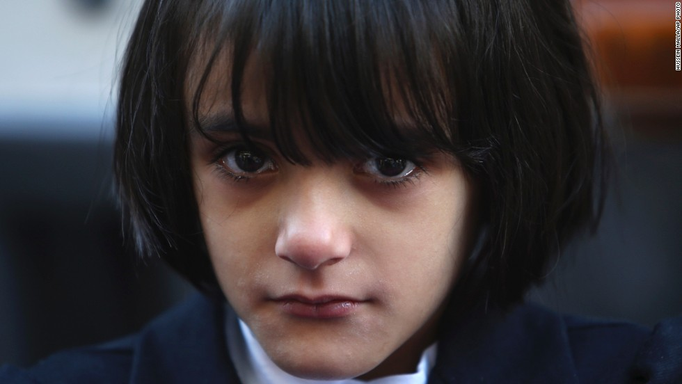 """OCTOBER 11 - BEIRUT, LEBANON: A Syrian girl weeps while waiting for her flight to Germany, where she has been accepted as a refugee. More than <a href=""""http://www.cnn.com/2013/10/03/world/meast/syria-civilians-displaced/index.html"""">100,000 civilians were killed and 7 million forced to flee their homes</a> during the two-year war. Recognizing its work in Syria, the <a href=""""http://www.cnn.com/2013/10/11/world/europe/norway-nobel-peace-prize-opcw-syria/index.html?hpt=hp_t1"""">2013 Nobel Peace Prize was awarded</a> to the Organisation for the Prohibition of Chemical Weapons."""