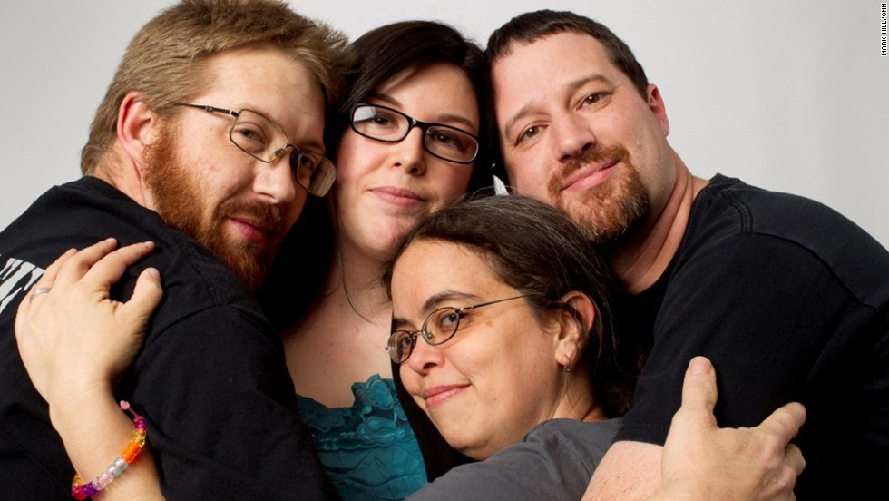 "To some, polyamory means more than an open relationship -- it's about having multiple committed relationships. Billy Holder, left, and wife Melissa Holder, second from right, live with their partner Jeremy Mullins, right. Pictured with them is Amy Munowitz, a friend who also identifies as ""poly."""