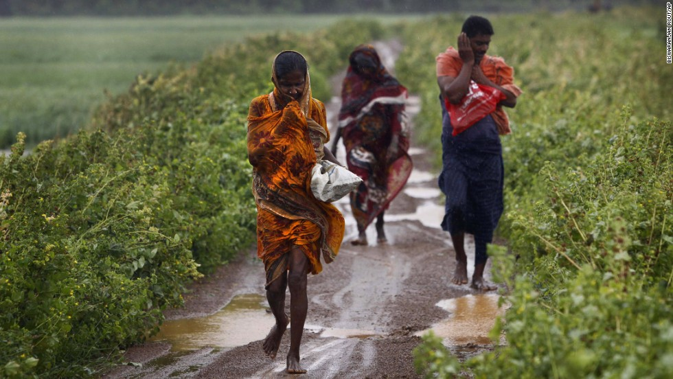 Villagers head for a cyclone center in the village of Podampeta, India, on October 12.