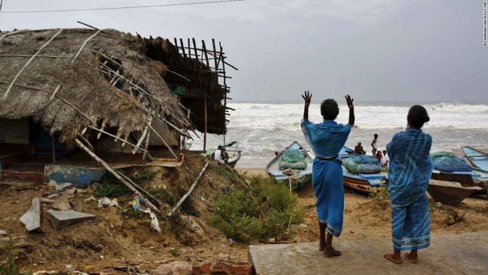 Indian women signal to fishermen to return following a cyclone alert before evacuating their village in Gokhurkuda on Friday, October 11.
