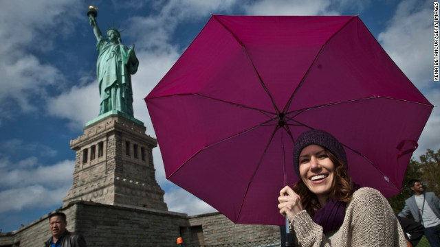 Tourists pose for pictures during a visit to the Statue of Liberty on Sunday in New York City.