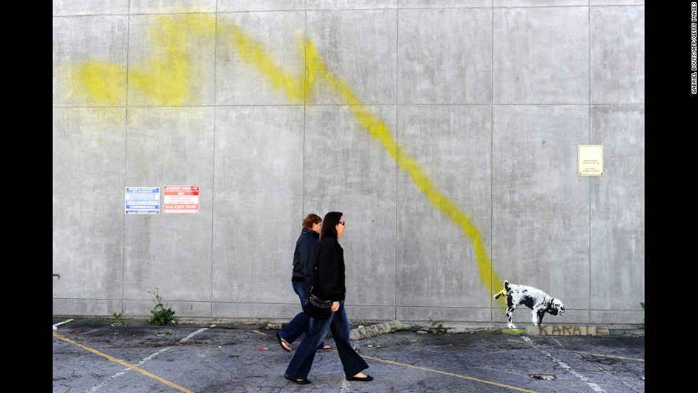 People walk past a Banksy painting of a dog urinating on a wall in Beverly Hills, California, in 2011.