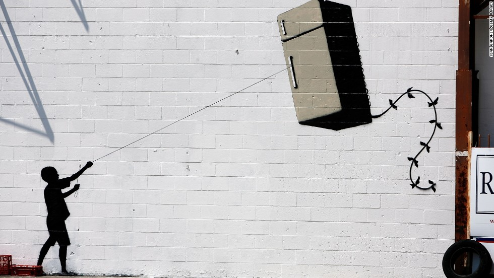 A silhouette of a child holding a refrigerator-shaped kite is seen on a wall in New Orleans in 2008.