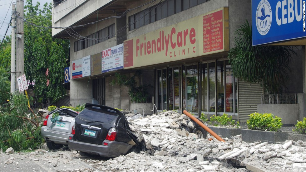 Cars lie under rubble outside the GMC Plaza Building in Cebu on October 15.