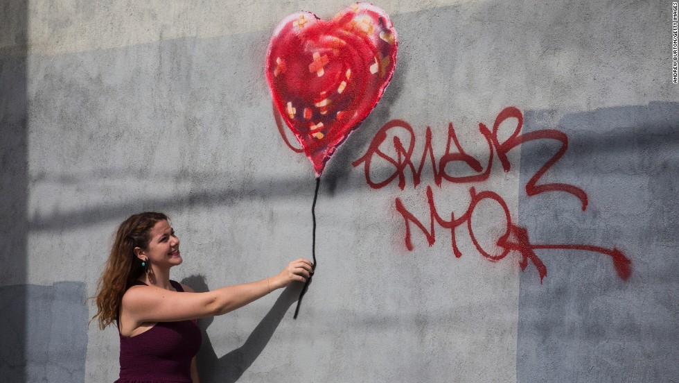A woman poses with Banksy's painting of a heart-shaped balloon covered in bandages. The piece, in the Red Hook neighborhood of Brooklyn, was defaced with red spray paint shortly after it was completed.