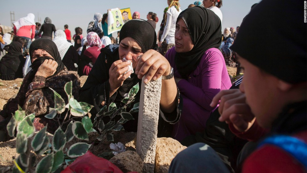 Kurdish women grieve during a visit to a cemetery in Derik, Syria, on Tuesday, October 15.