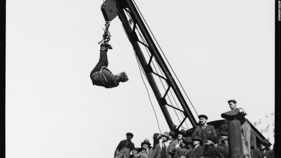 Houdini performs a straitjacket escape dangling from a crane in Manhattan in the 1910s.