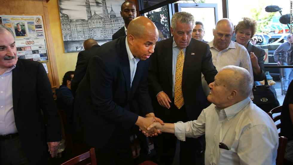Booker greets a man while campaigning in downtown Newark on October 15.