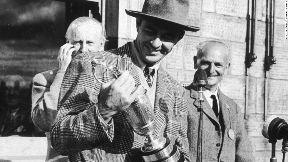 The late American golfer Sam Snead holds the 1946 British Open Golf Championship trophy in St. Andrews, Scotland. His family sold the claret jug he won at the open this year for $262,900. His relatives are not alone. Many retired big-name athletes are cashing in by selling their sports memorabilia.