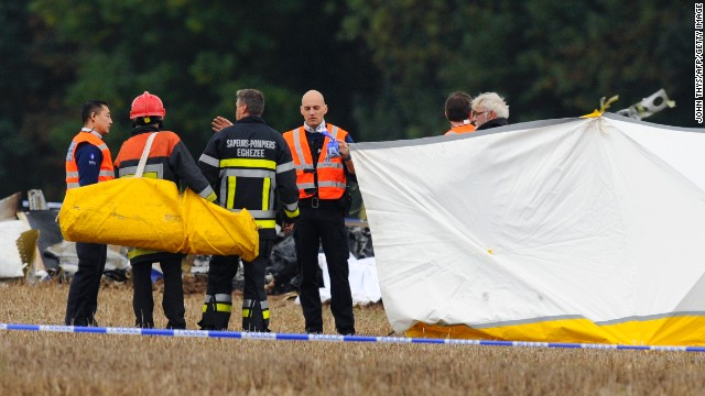 Belgian firefighters investigate at a site where a plane carrying 10 parachutists crashed shortly after takeoff, October 19, 2013.