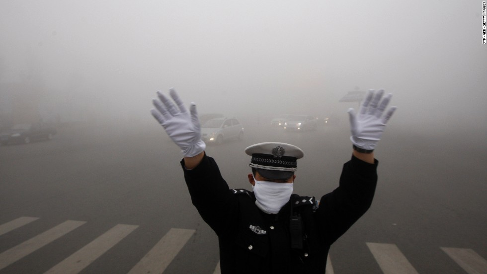 A policeman directs Harbin traffic on Monday, October 21. In some central areas of the city, visibility was less than 20 meters (65 feet).