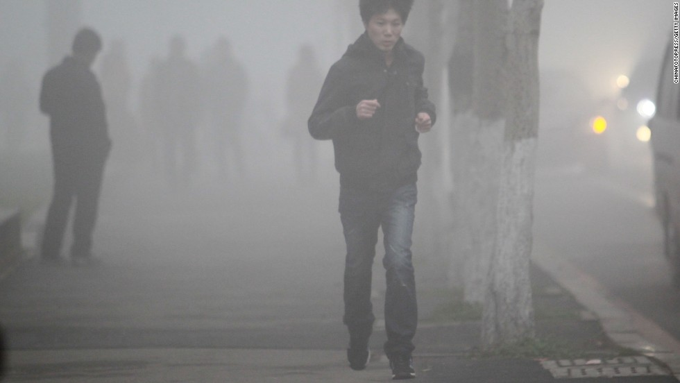 A man runs along a foggy road in Changchun, China, on October 21.