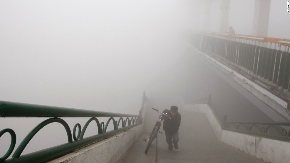 "OCTOBER 22 - HEILONGJIANG PROVINCE, CHINA: A man pushes his bike up a bridge during a day of extremely heavy smog. Visibility shrank to less than half a football field and <a href=""http://www.cnn.com/2013/10/22/world/asia/china-smog-lingers/index.html?hpt=ias_c2"">small-particle pollution soared to a record 40 times the international safety standard</a> in the northern Chinese region."
