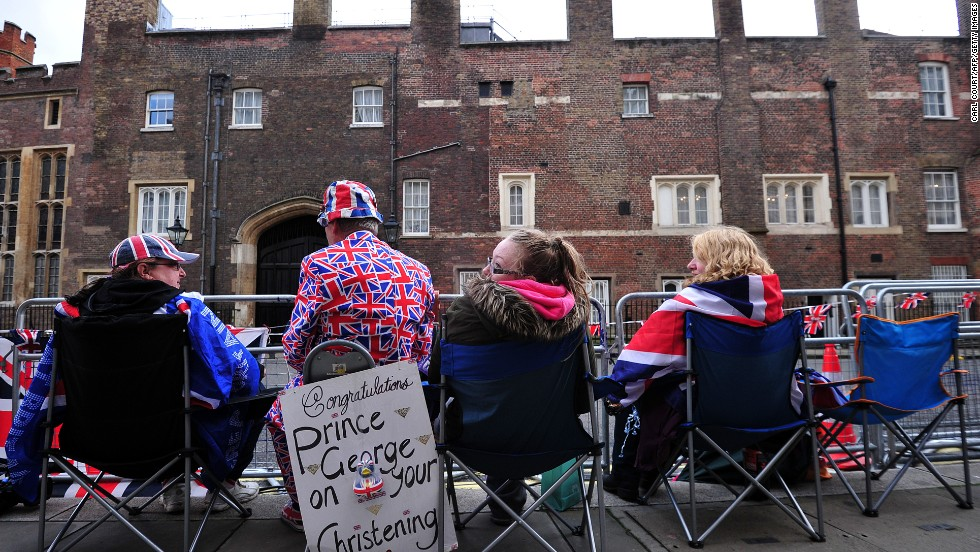 Spectators sit across from St. James' Palace as they wait for the royal family to arrive for the christening.