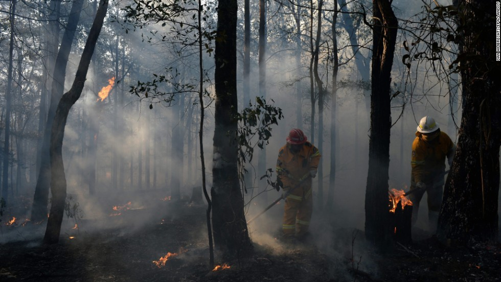 New South Wales Rural Fire Service crews mop up an area after stopping a fire in Bilpin in the Blue Mountains of Australia on October 23.