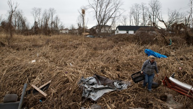 Carol Mittelsdorf looks through debris to find keepsakes that may have washed away after the storm.