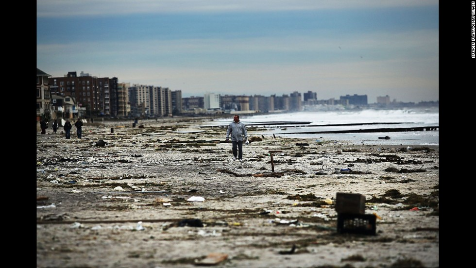 A man walks along the heavily damaged Rockaway beach on November 2, 2012.