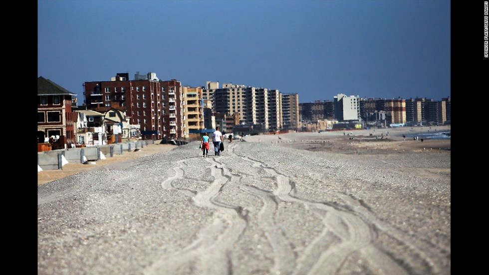 People walk down the Rockaway beach on October 23.