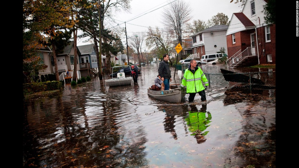 An emergency worker uses a boat to help two people evacuate after their neighborhood was flooded on October 30, 2012, in Little Ferry, New Jersey.