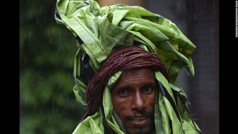 An Indian rickshaw puller covered with plastic walks through a street during the heavy rains in Kolkata, India, on Saturday, October 26. Earlier this month, a cyclone struck the eastern coast and is now involved with mass flooding that has forced thousands to flee their homes and seek refuge in shelters.