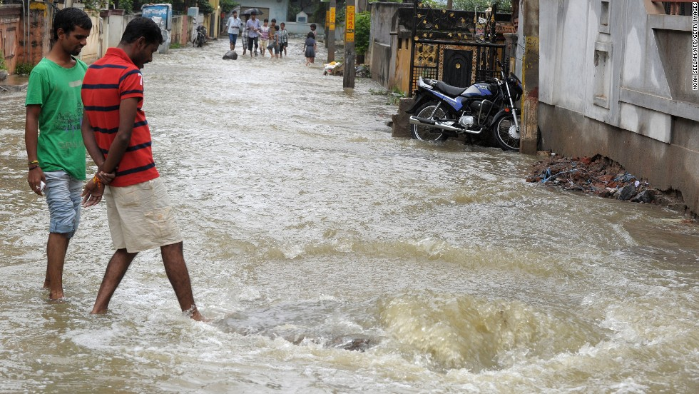 Pedestrians wade on a flooded street following heavy rain in Saroornagar on October 25.