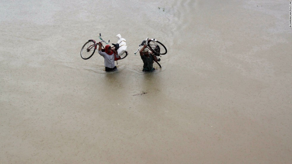 Two villagers carry their bicycles and wade through floodwaters in Banapur village in the eastern Indian state of Orissa on October 25.