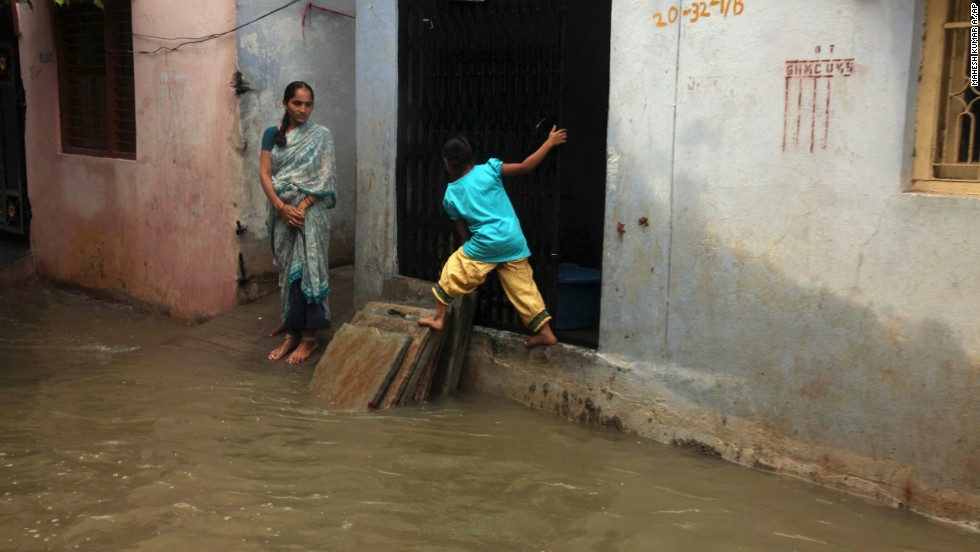 A child balances herself on dry area as she crosses a flooded street in Hyderabad on October 25.