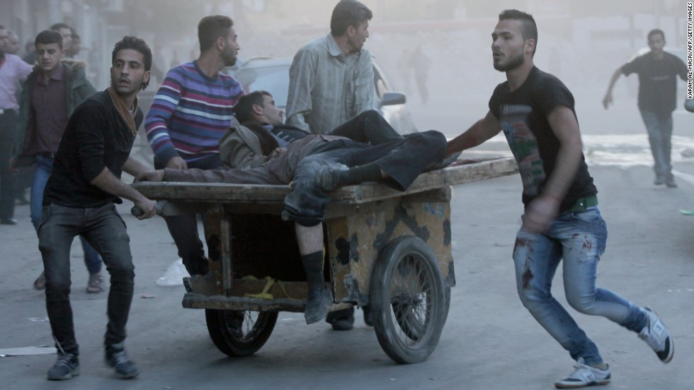 Two injured men are transported on a cart in  Aleppo, Syria, following shelling as fighting between pro-government forces and rebels continues on Saturday, October 26.